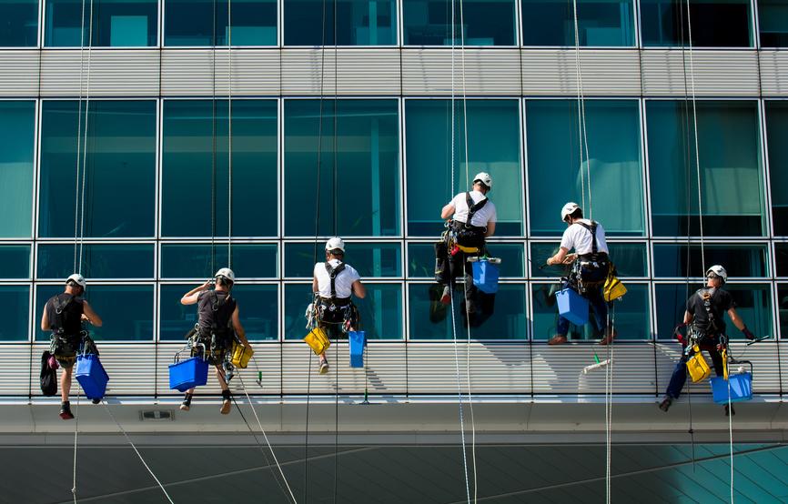 Team von kletternden Arbeitern auf Brohaus Fassade