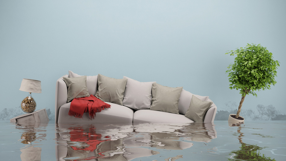 Wasserschaden nach Hochwasser im Haus mit Sofa im Wohnzimmer